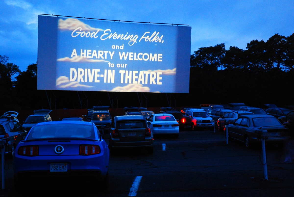 drive-in theater screen welcoming moviegoers in cars