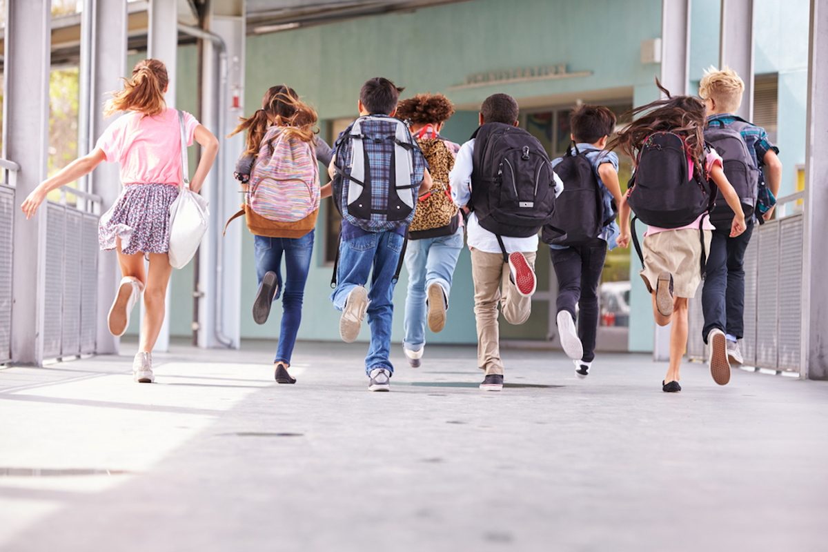 group of kids running into school, photo taken from behind