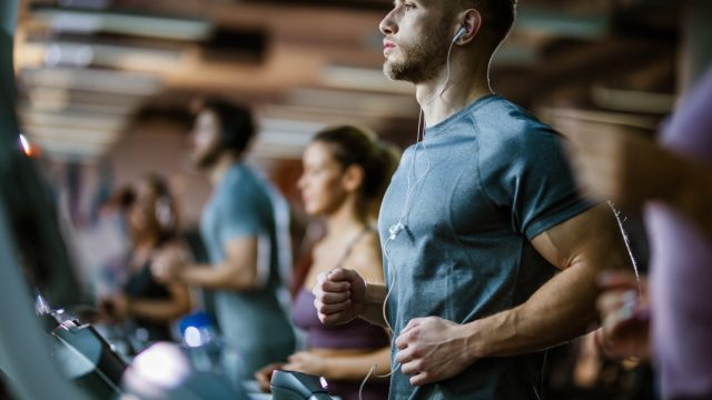 Young male athlete listening music while exercising on treadmill in a gym.