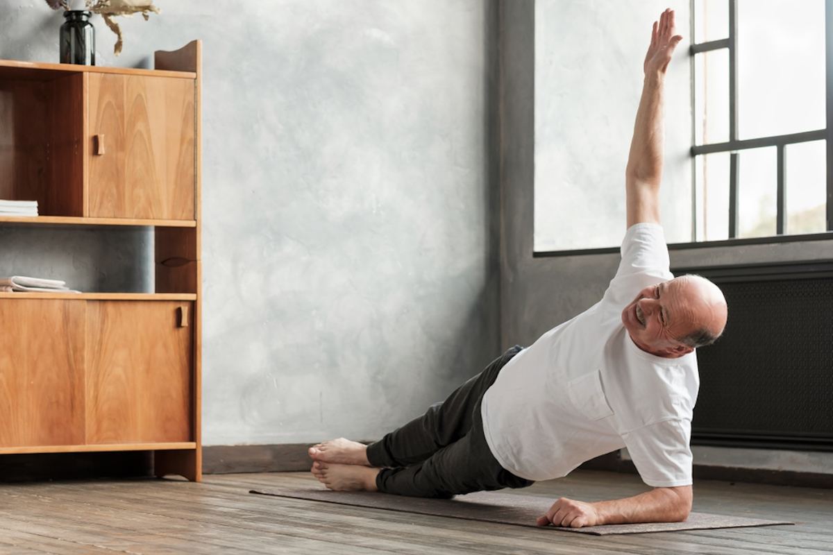 senior man man doing a side plank exercise at living room