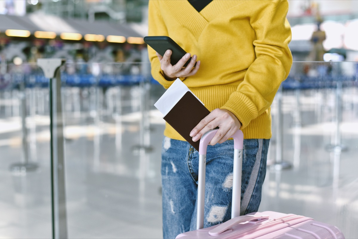 man holding plane tickets and suitcase in airport