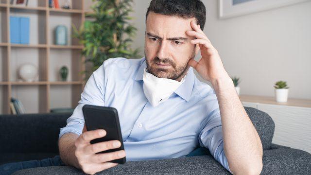 Worried man at home reading phone with mask no chin amid coronavirus