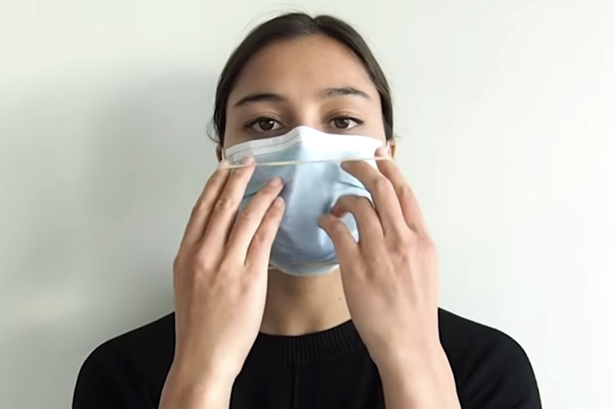 woman putting a mask on her face