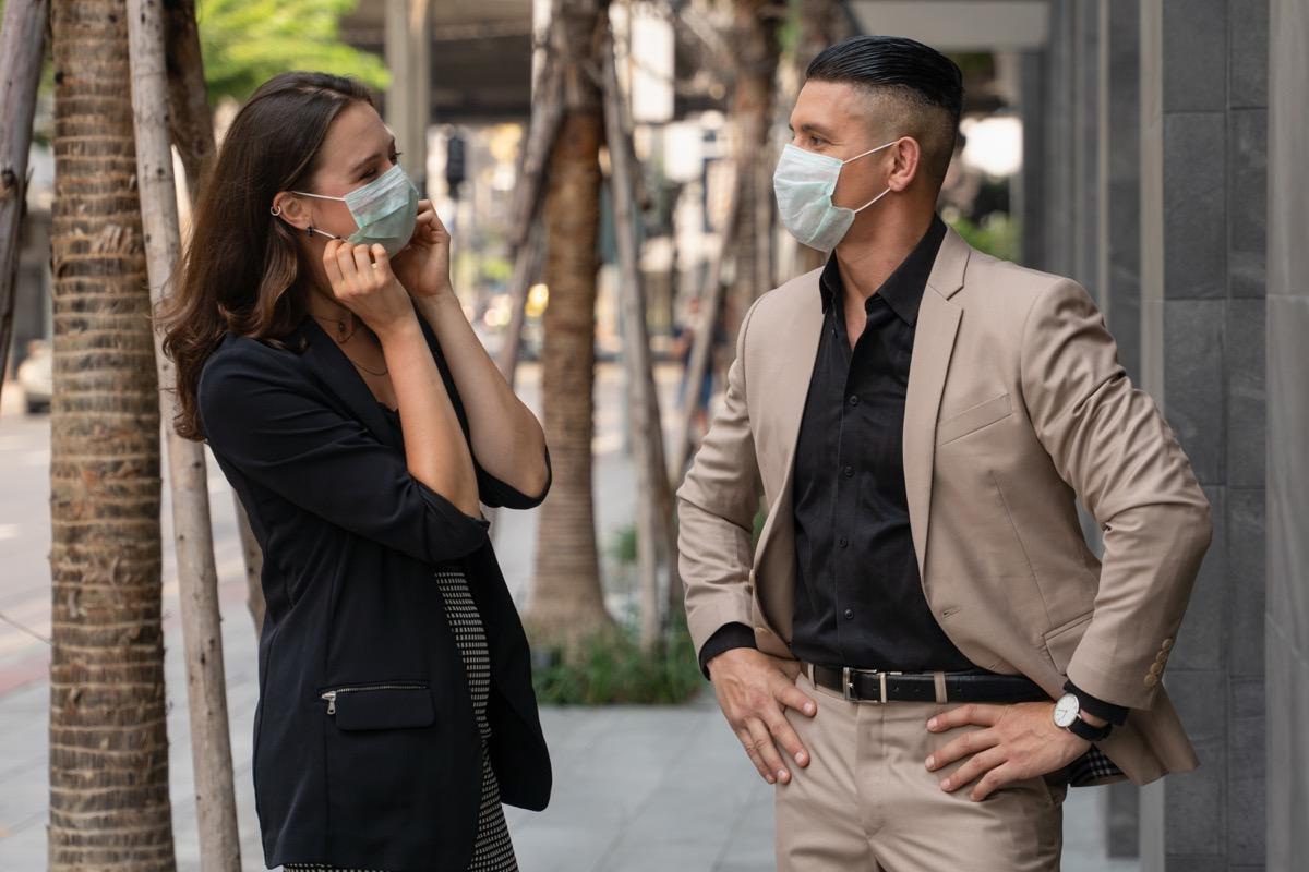 man and woman talking while wearing masks