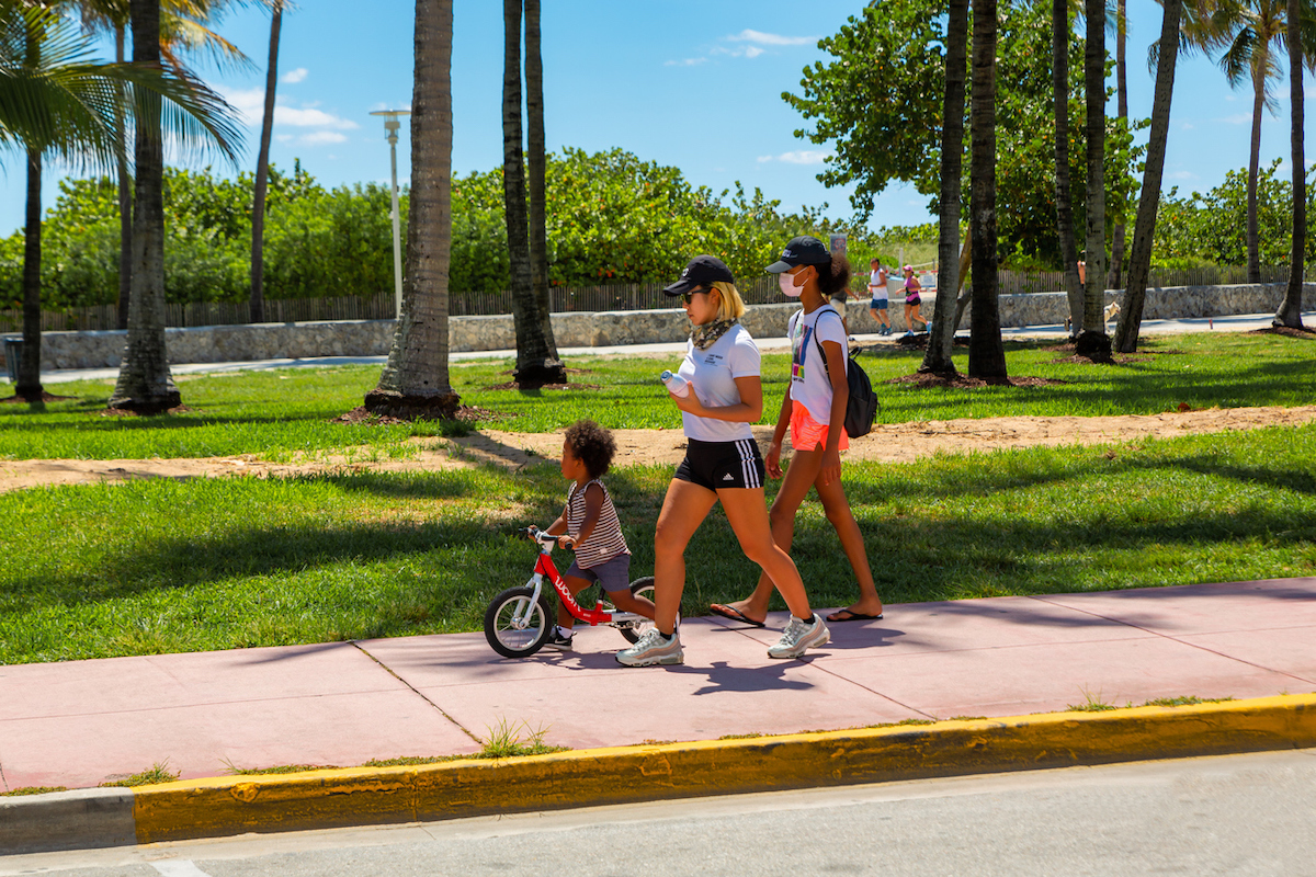 Two teenager girls in face masks walking outdoors in Miami Beach with young boy amid coronavirus pandemic