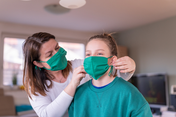 A mother wearing a green homemade protective face mask puts the same style of mask on her daughter