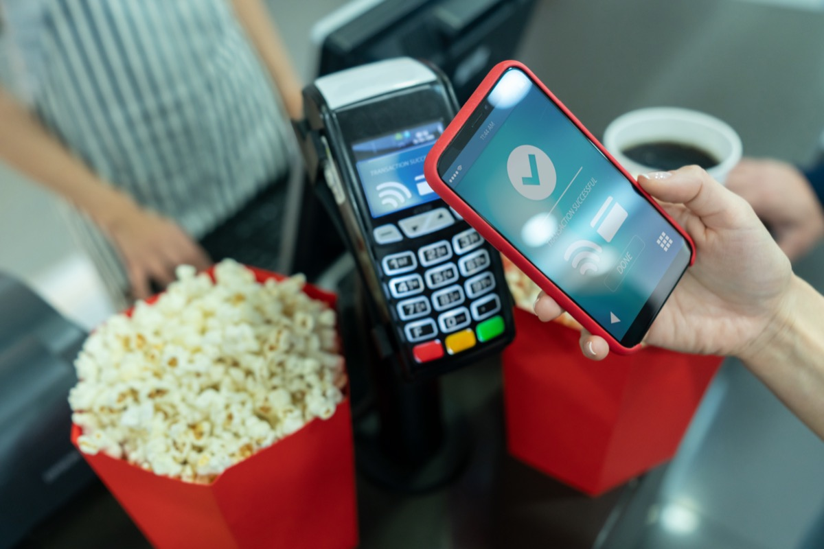 Close-up on a customer making a contactless payment at the concession stand at the cinema using a cell phone