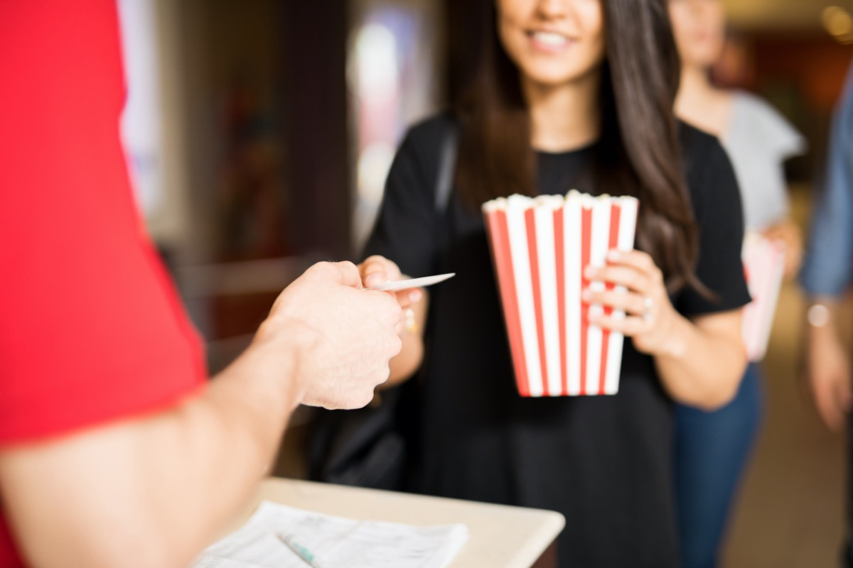 woman gives a movie ticket to a box office attendant