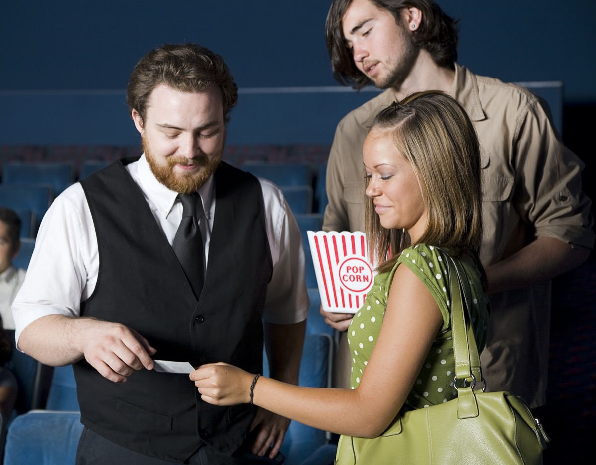 A young couple with an usher in a movie theater.