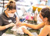 woman getting a manicure through a shield at a nail salon