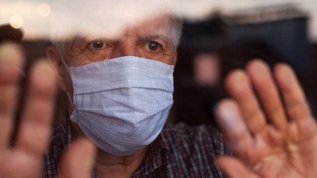 Old man looking out window with mask on