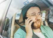 Young Man Riding on a Passenger Seat of a Car Makes a Phone Call, Talks with Clients, Customers and Business Associates. Camera Shot from Outside the Vehicle.