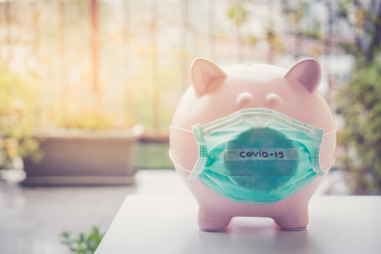 A piggy bank on a table top wearing a face mask that says COVID-19