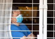 man looking out window as he's quarantined