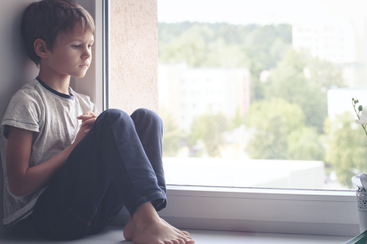 sad child sitting by a window
