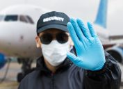 Security guard with face mask in front of airplane