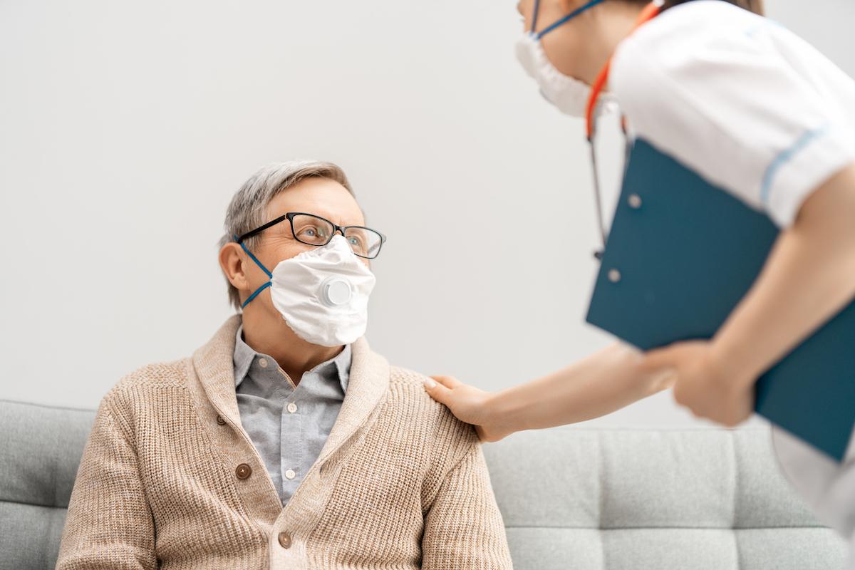 Doctor and senior man wearing face masks during coronavirus outbreak.