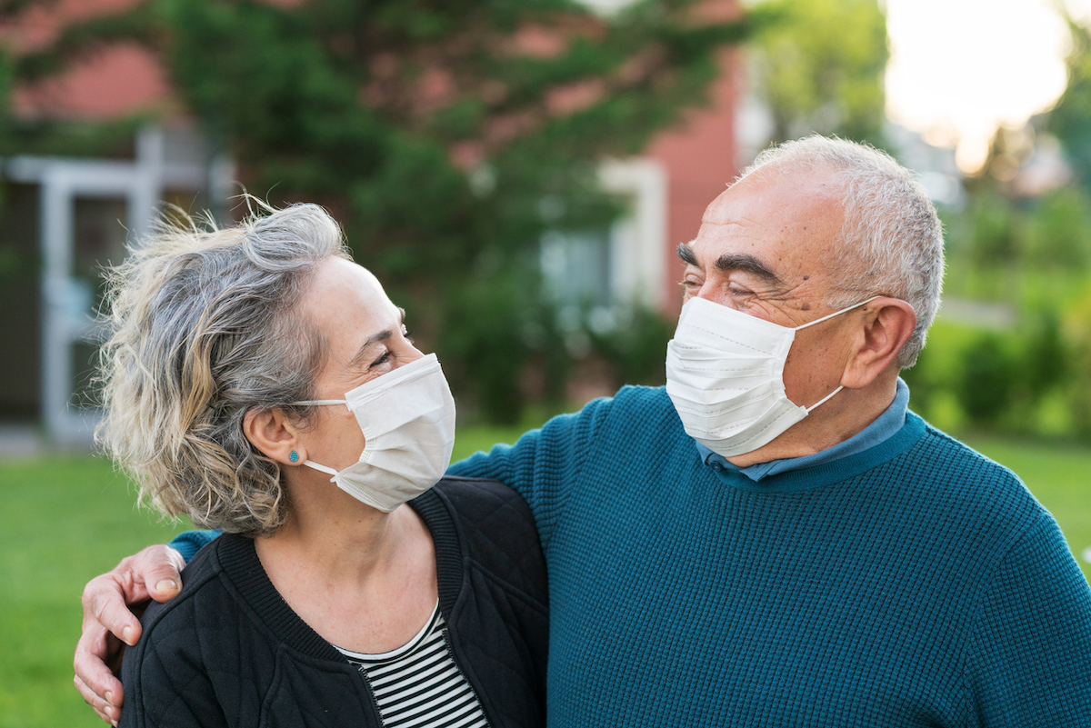 senior couple Couple wear surgical masks and smiling at each other