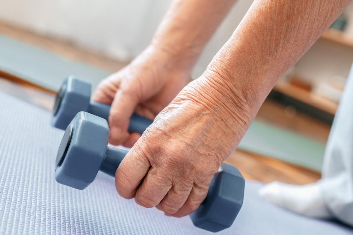 Senior man exercising indoors holding dumbbells down near the floor