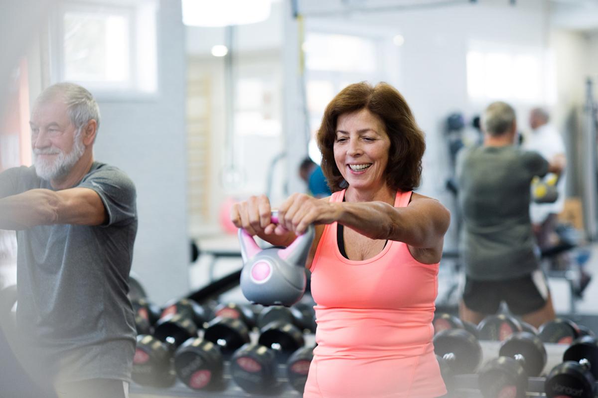 senior man and senior woman lifting weights at the gym