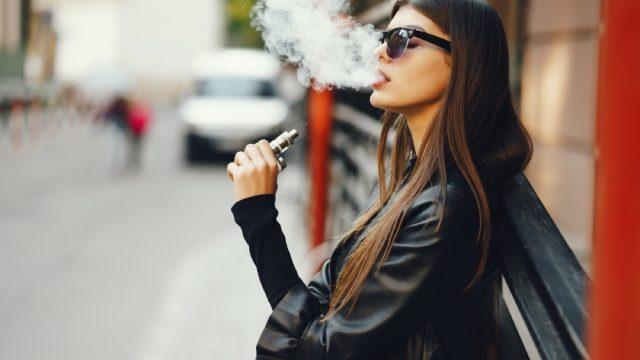 young white woman smoking an e-cigarette outside