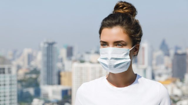 white woman with face mask standing on roof with city skyline in the background