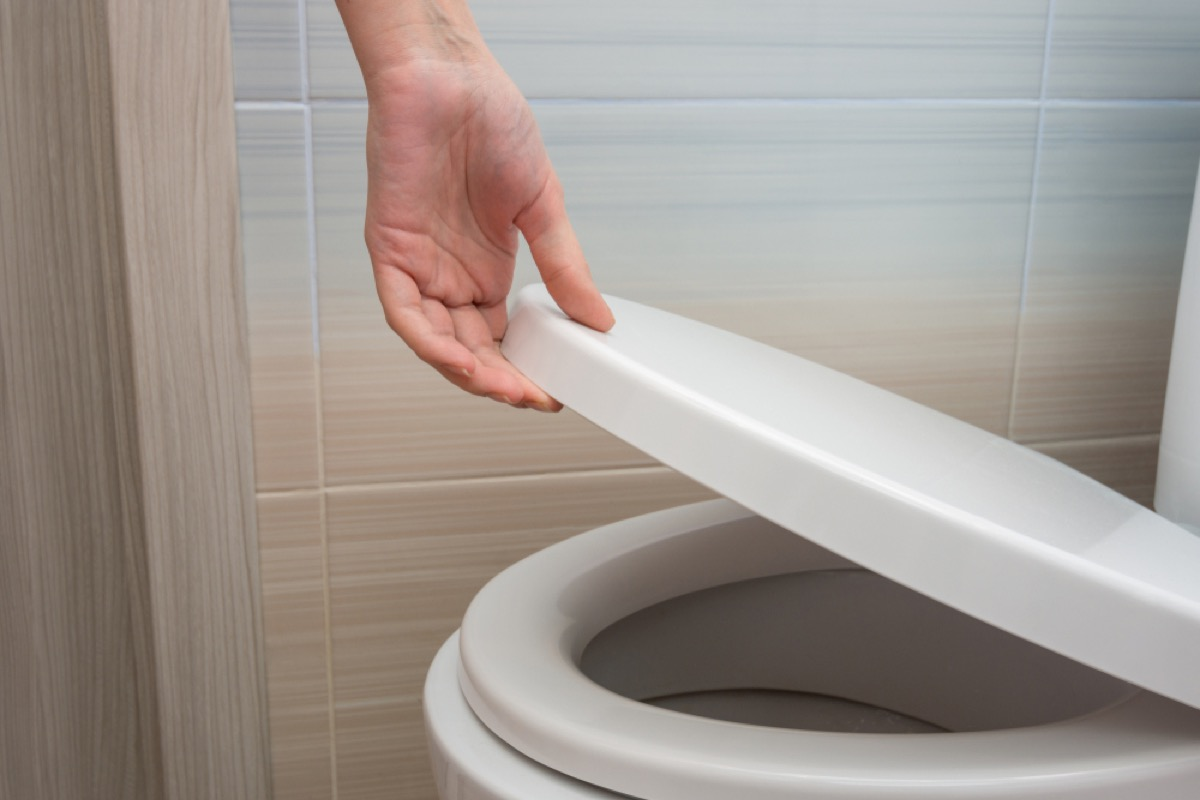 close up of hand lowering toilet seat