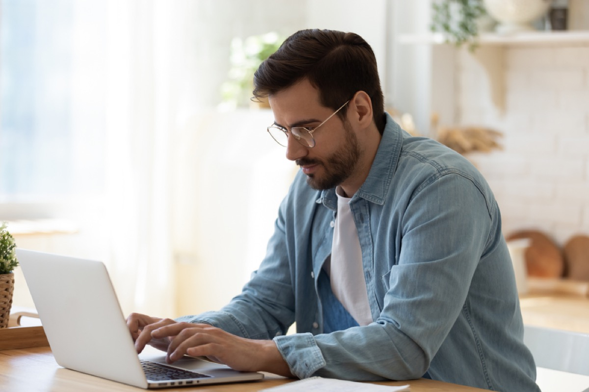 white man sitting and typing on his laptop while leaning forward