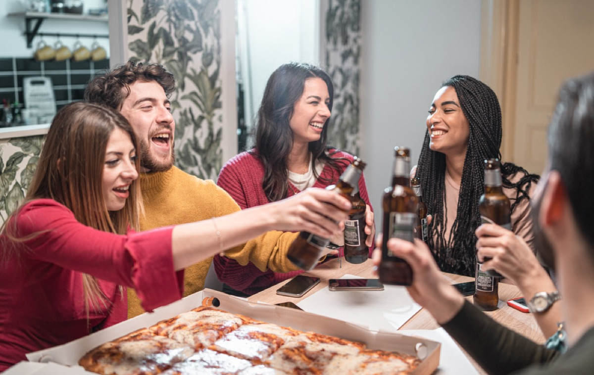 group of young people toasting beer and eating pizza