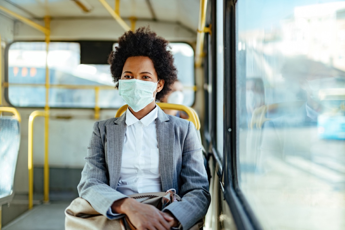 young black woman with a face mask on a bus