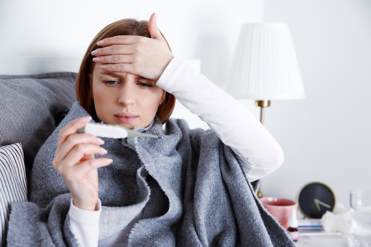 white woman touching her forehead and reading a thermometer under a blanket