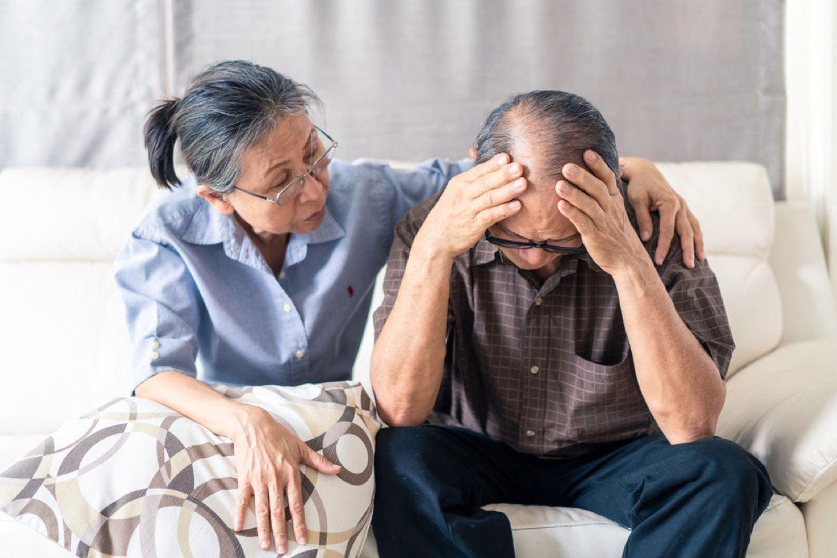 older asian woman comforting older asian man on couch