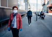 older woman with face mask walking on sidewalk with another woman walking behind
