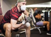 white man with face mask and gloves lifting weights at the gym