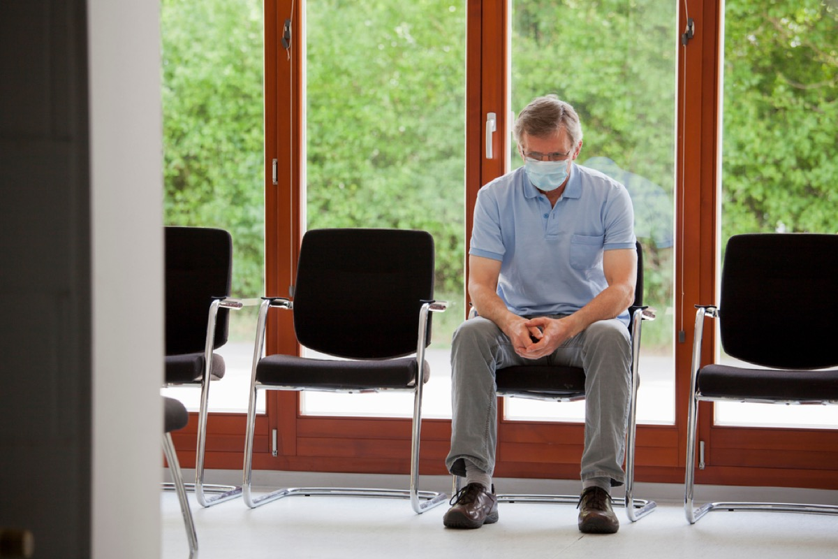 older white man with face mask sitting in waiting room