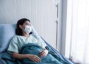 Woman with a face mask in a hospital bed looking out the window