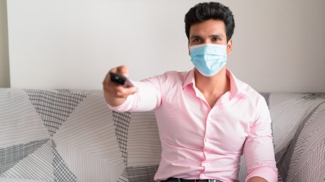 man watching tv and holding remote while wearing a mask