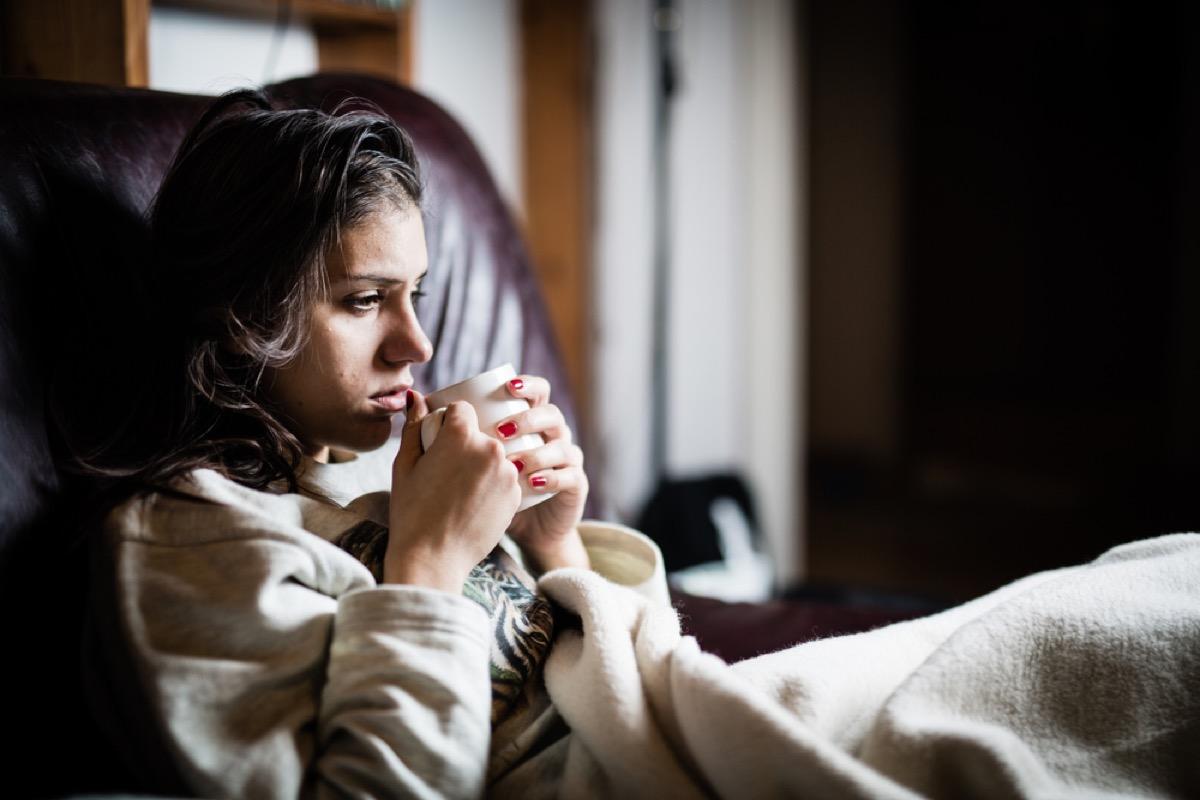 sick white woman drinking tea under a blanket