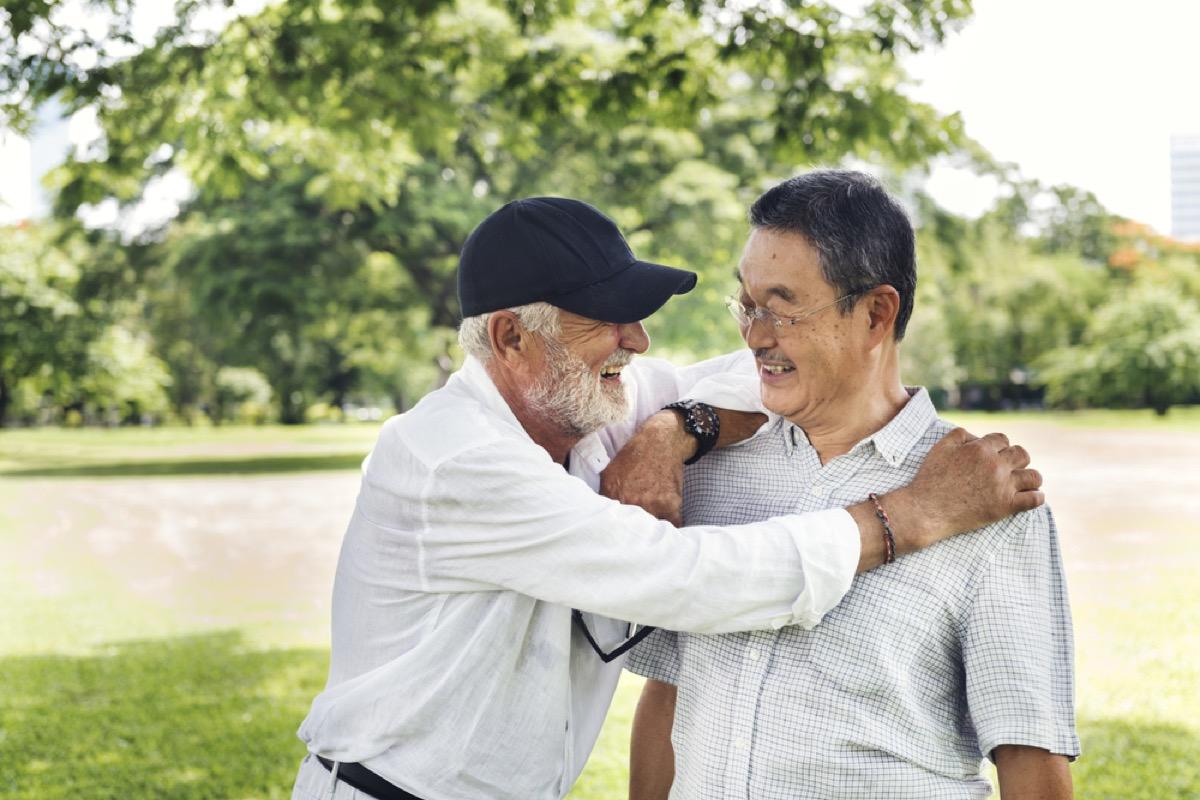 older white man embracing older asian man in park