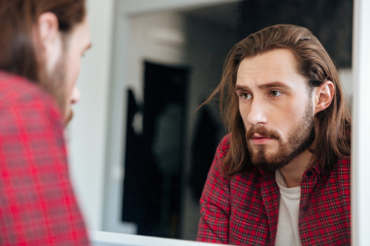 young bearded white man looking seriously in the bathroom mirror