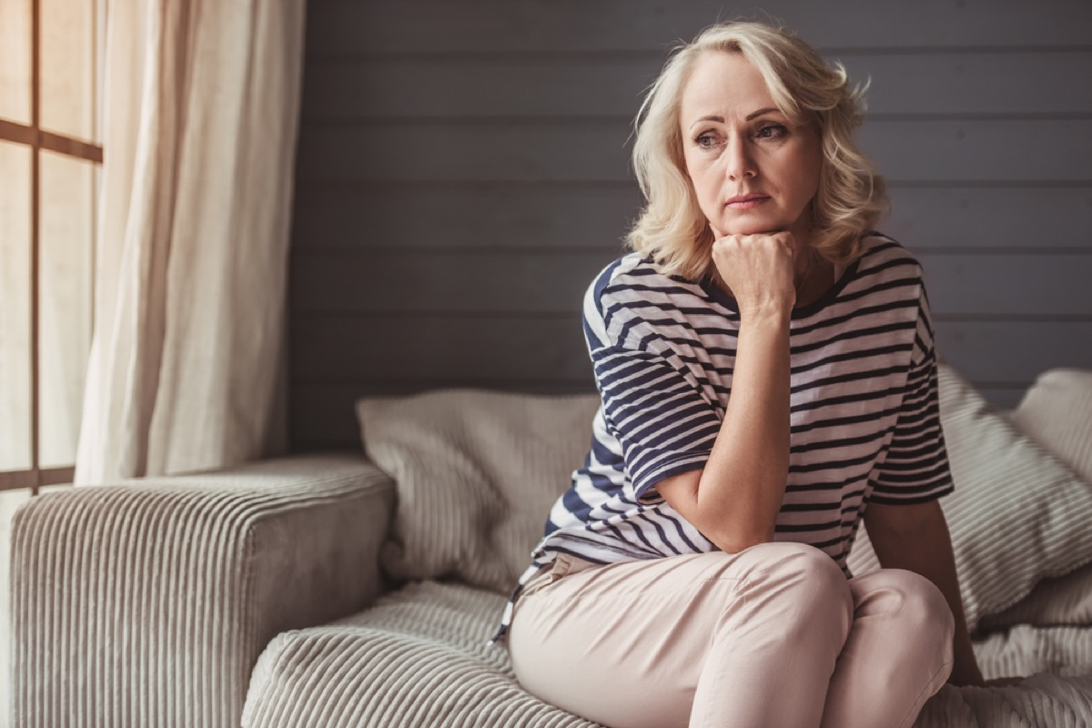 sad older white woman sitting on a couch