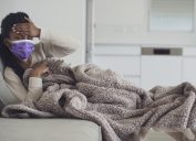 A young woman wearing purple face mask lying on the couch under a blanket and checking her forehead for a fever