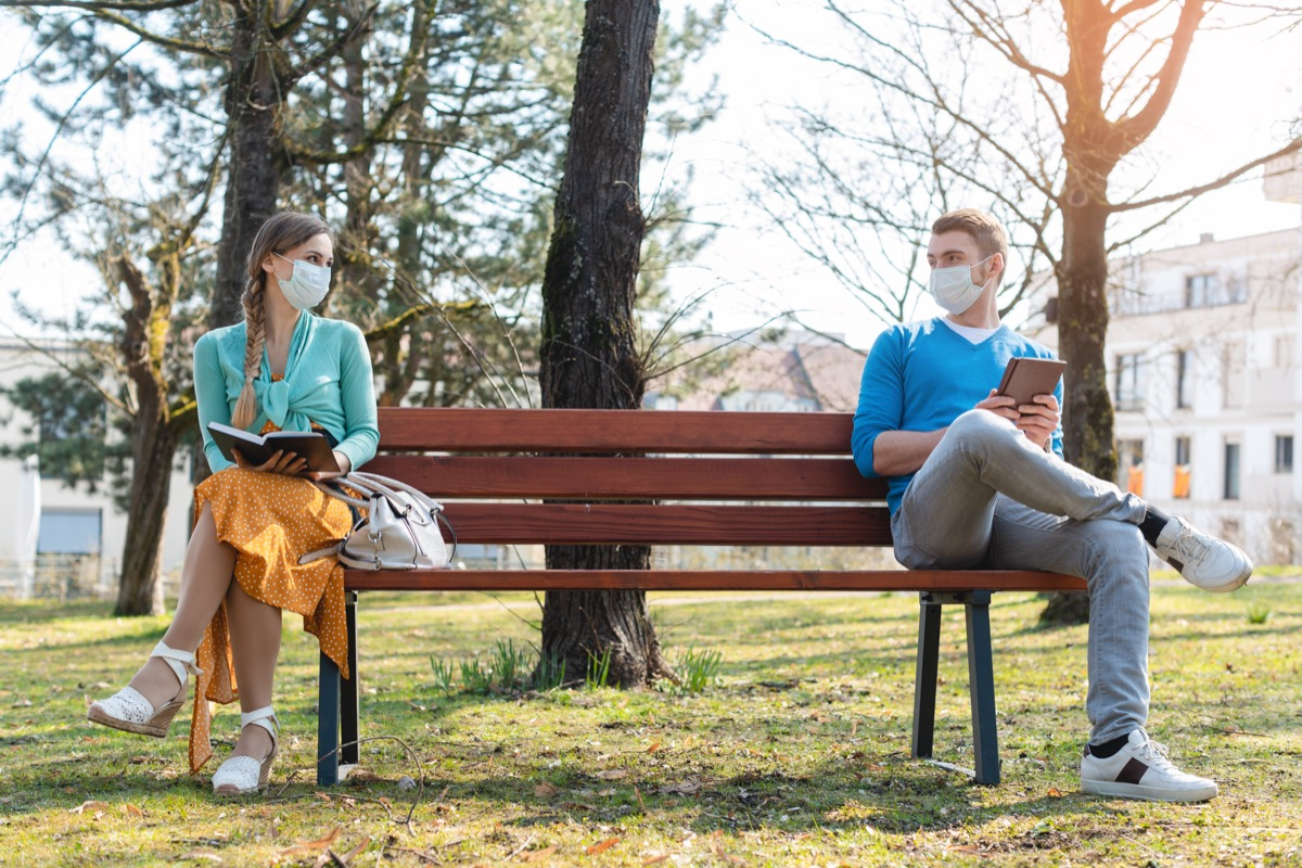 man and woman social distancing on bench