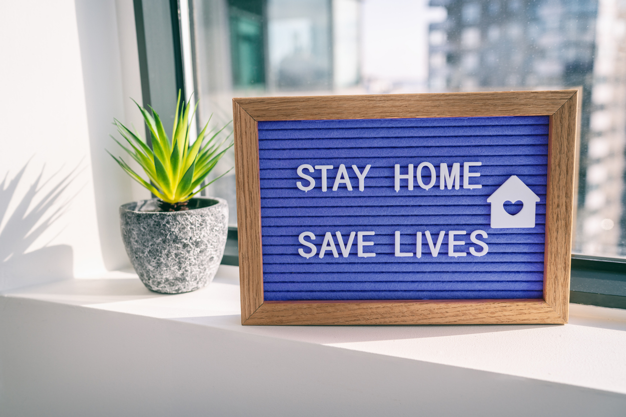 A blue sign on a windowsill that says stay home save lives