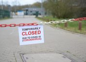 Red white chain barrier and sign with text Temporarily Closed due to Covid-19 Coronavirus, in front of a blurred company, countrywide pandemic lock down, copy space, selected focus