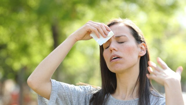 Woman drying sweat using a wipe in a warm summer day
