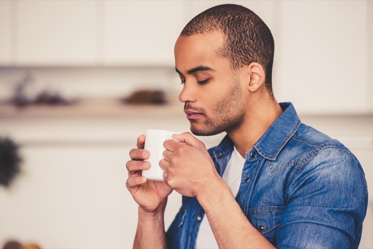 man smelling cup of tea