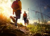 three hikers walk on a grassy trail