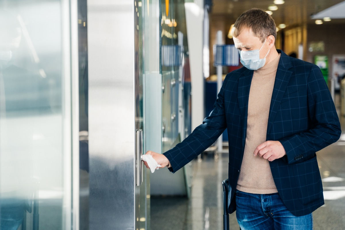 Man protects hands from direct contact with door handle, uses paper napkin from conntracting virus through contact with surface, wears disposable medical mask to prevent covid19, poses in public place