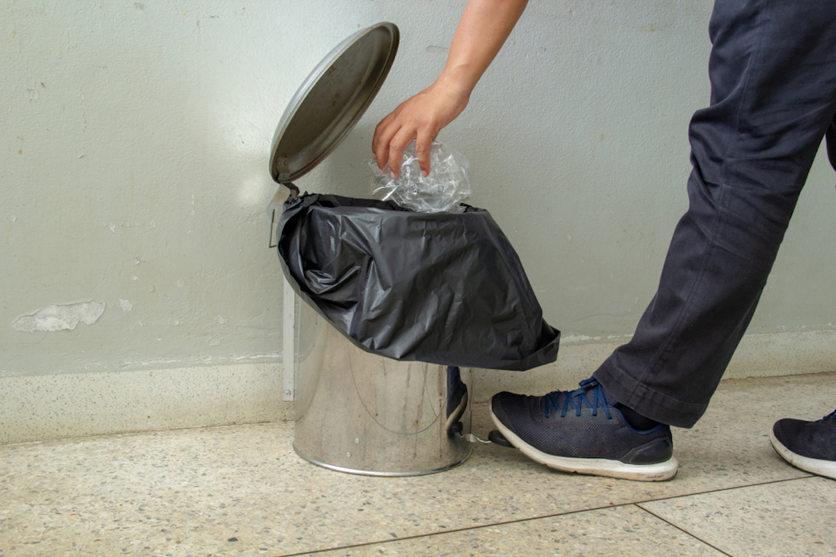 foot pushes pedal of touchless trash can